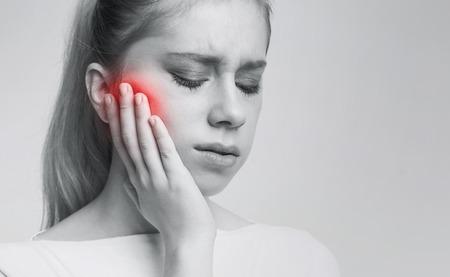 Igiene dentale. Giovane donna che soffre di dolore ai denti, carie, foto in bianco e nero con guancia dolorante rossa, spazio libero