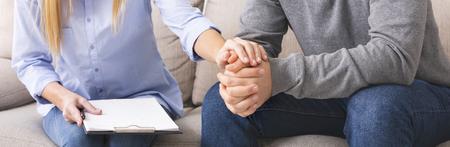 Ayuda profesional. Psicóloga apoyando a su paciente deprimido en sesión de terapia, panorama Foto de archivo