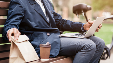 Lunch break. Businessman sitting outdoors with laptop and bicycle nearby, crop