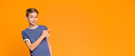 Wow, look. Emotional teen boy pointing aside at empty space, orange panorama background