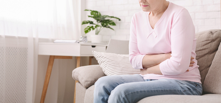 Unhappy senior woman holding stomach, suffering from abdominal pain at home, panorama, empty space