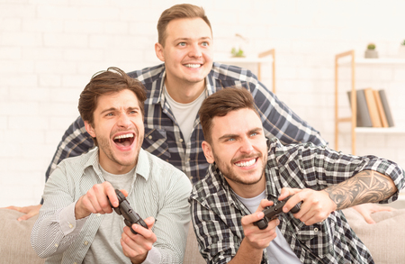 Avid gamers. Excited men playing video game, meeting and having fun at home
