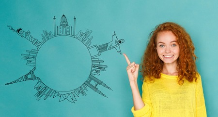 Young redhead woman pointing the finger at drawn circle from world sights simbols on blue background, copy space. World tour concept