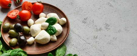 Mozzarella cheese, cherry tomatoes, olives and basil leaves on wooden plate over concrete background. Mediterranean traditional products concept Stock Photo