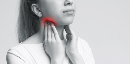 Young woman suffering from tonsillitis, pulping her neck, monochrome panorama photo, free space