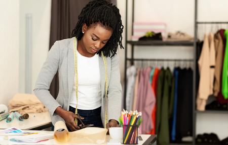 Diseñador de moda trabajando en estudio, dibujo de corte, vestido de costura