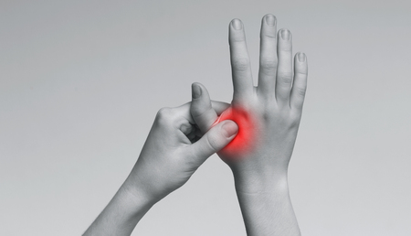 Young woman suffering from pain in palms, massaging her painful hand from symptoms of Peripheral Neuropathy