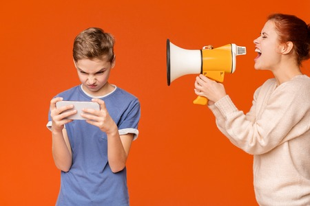 Angry woman shouting through megaphone at addicted boy playing on cellphone, orange background Stock Photo - 121163305