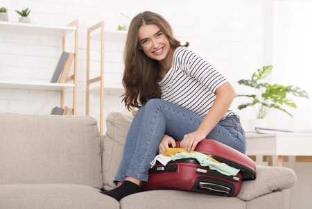 Preparing for holidays. Woman trying to close suitcase on sofa