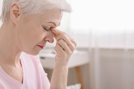 Fatigued senior woman massaging nose bridge, feeling eye strain or headache trying to relieve pain, thinking of problems, empty space