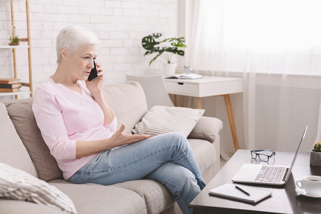 Call to customer support service. Angry senior woman talking by phone, complaining about problems with laptop and internet connection, empty space Stock Photo