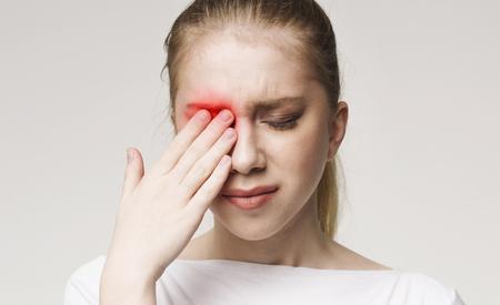 Mujer molesta que sufre de un fuerte dolor en los ojos. Concepto de salud, panorama
