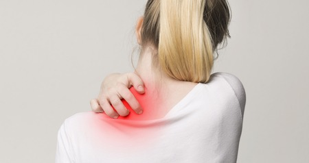 Woman scratching her shoulder and neck because of dry skin, back view Stock Photo