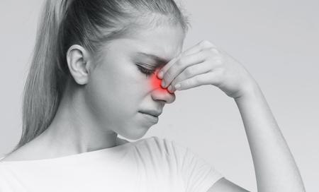 Frustrierte junge Frau, die unter Sinusdruck leidet und ihre Nase mit geschlossenen Augen berührt, monochromes Foto Standard-Bild
