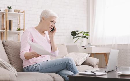 Boze senior vrouw praten aan de telefoon en thuis werken, laptop kijken en papieren correspondentie zwaaien, thuis zitten, vrije ruimte Stockfoto