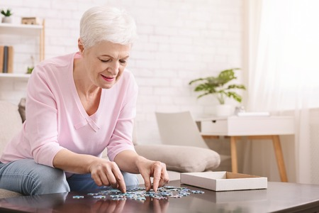 Activity can improve brain function. Elderly woman sitting at table and sorting jigsaw puzzle pieces, free space Imagens