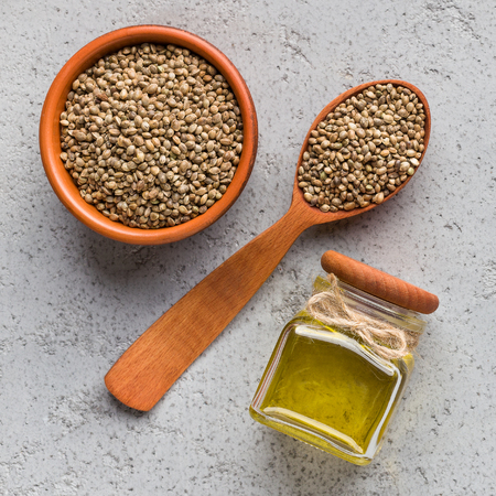 Hemp oil in bottle and hemp seeds in bowl and spoon over concrete background, top view. Super food concept Reklamní fotografie