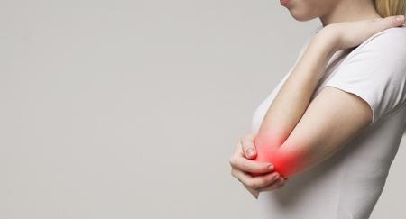Mujer que sufre de reumatismo articular crónico. Concepto de tratamiento y dolor de codo