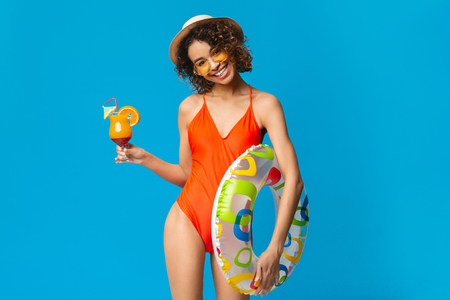 Happy millennial african american woman in swimming suit holding summer cocktail and swim ring, blue studio background