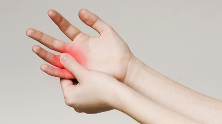 Pain and numbness in fingertips and palms. Woman massaging her sore hand, panorama