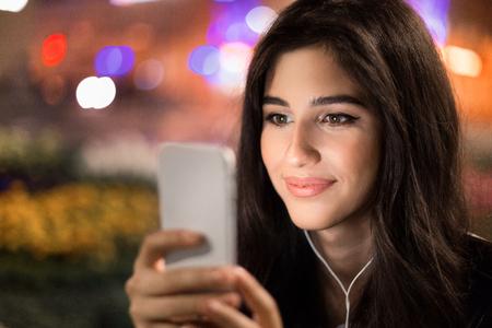 Choosing songs. Woman listening music on smartphone walking at night in city