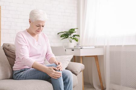 Problemy zdrowotne starości. Starsza kobieta cierpiąca na ból w nodze, masująca kolano w domu, pusta przestrzeń