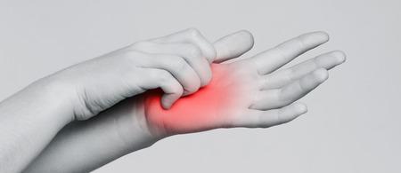 Dermatitis. Jonge vrouw die jeuk aan haar hand krabt, zwart-wit panoramafoto