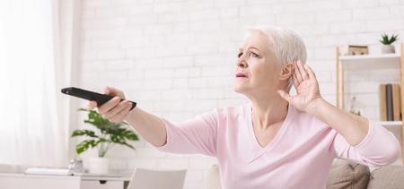 Ältere Frau macht Hörzeichen, steigende Lautstärke des Fernsehers mit Fernbedienung, Panorama,
