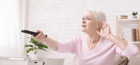 Elderly woman making hearing sign, rising tv set volume with remote control, panorama