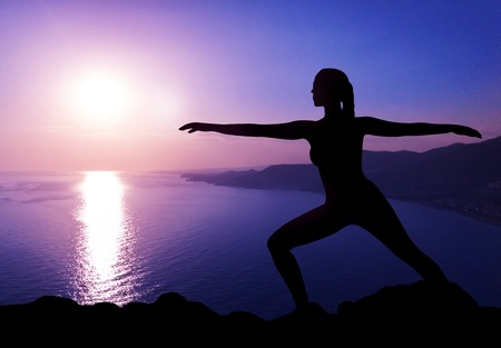 Silhouette of woman practicing yoga at sunset. Yoga retreat concept
