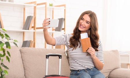 Enjoy traveling! Woman taking selfie with tickets, waiting for taxi at home