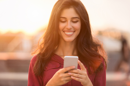 Happy woman walking in city, texting on smartphone at sunset Stock Photo