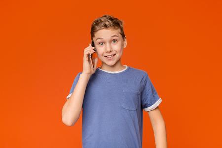 Positive teen boy talking on mobile phone, got good news, orange studio background
