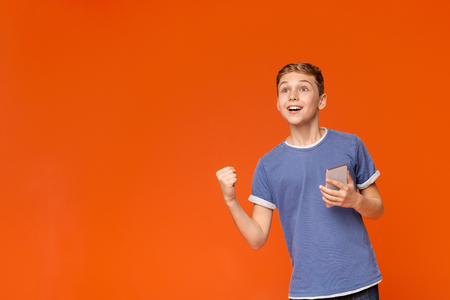 Happy teen boy screaming in fascination, holding mobile phone in hand and cheering on orange background 스톡 콘텐츠