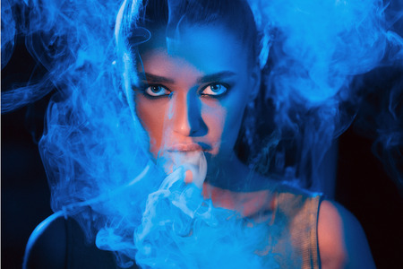 Young woman smoking vape or e-cigarette in neon blue light