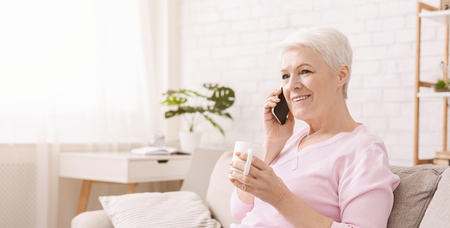 Lovely senior lady having fun conversation with her friend or relative, drinking coffee at home, panorama, empty space