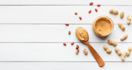 Peanut butter in jar and spoon and scattered peanuts on white wooden background, top view, copy space. Artisan peanut butter concept