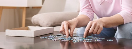 Elderly female hands trying to connect pieces of jigsaw puzzle. Creative idea for Alzheimers disease, dementia, memory loss and mental health concept
