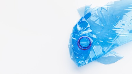 Crampled plastic bottle in fish shape on white background. Save ocean concept