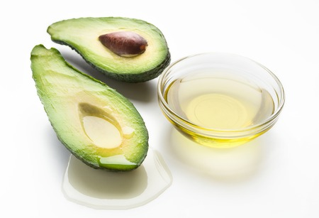 Fresh sliced avocado and oil in bowl on white background