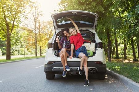 Ragazze felici sedute in macchina aperta indietro con gesto di saluto. In viaggio con il concetto di amici, copia spazio