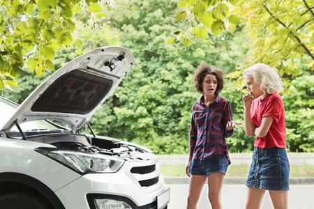 Two upset girls standing near broken car on countryside road Reklamní fotografie