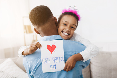 Little girl hugging dad and giving him postcard, congratulating with fathers day Stockfoto