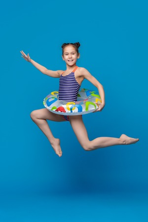 Happy child girl in swimsuit jumping with swimming ring on blue studio background
