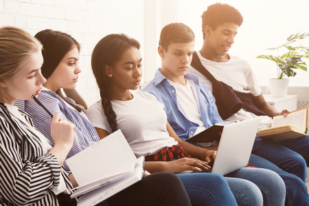 Multiethnic students preparing for exams with laptop and books in home interior