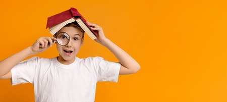 Discovering world through literature. Boy hiding under book and looking through magnifying glass, orange panorama background with empty space