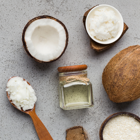 Fresh chopped coconut, coco flesh and jar with coconut oil on concrete background, top view. Extra virgin oil concept