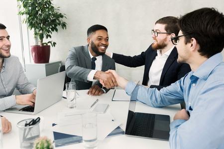Équipe heureuse félicitant le travailleur réussi en serrant la main, se réunissant au bureau Banque d'images