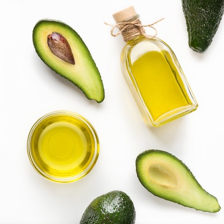 Sliced avocadoes and oil in bowl and bottle on white background top view. Vegetarian oils concept Archivio Fotografico