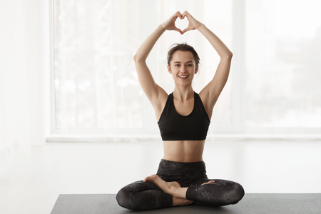 Love Yoga. Woman In Lotus Position, Holding Hands In Heart Shape Over Window